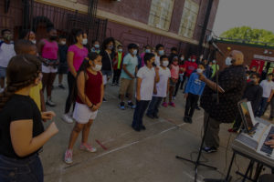 Music teacher conducts choir outside of a school.