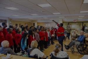 A student choir performs at a nursing home.