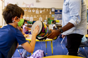A student pats a drum during music class.