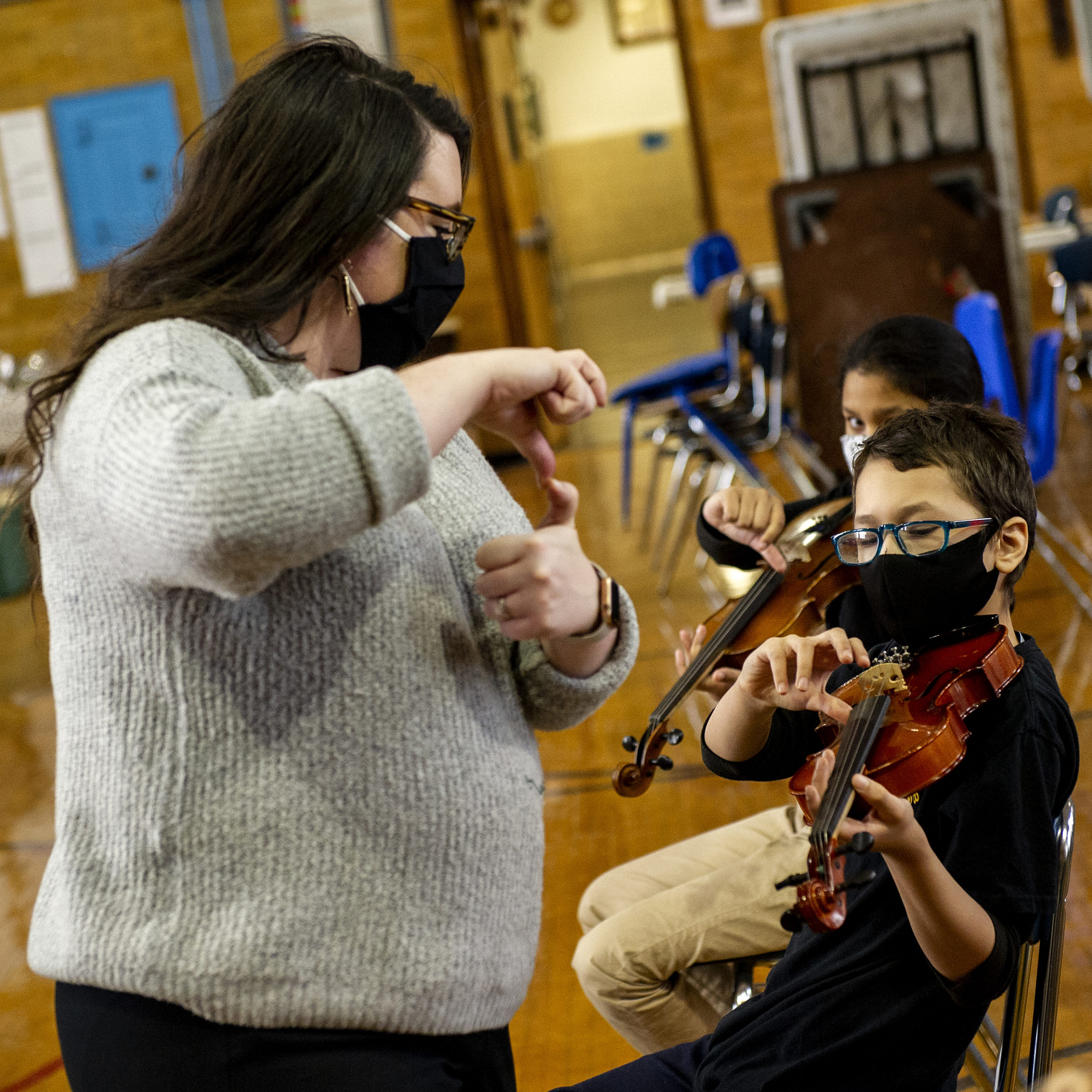 A music teacher instructs a student on how to pluck violin strings.